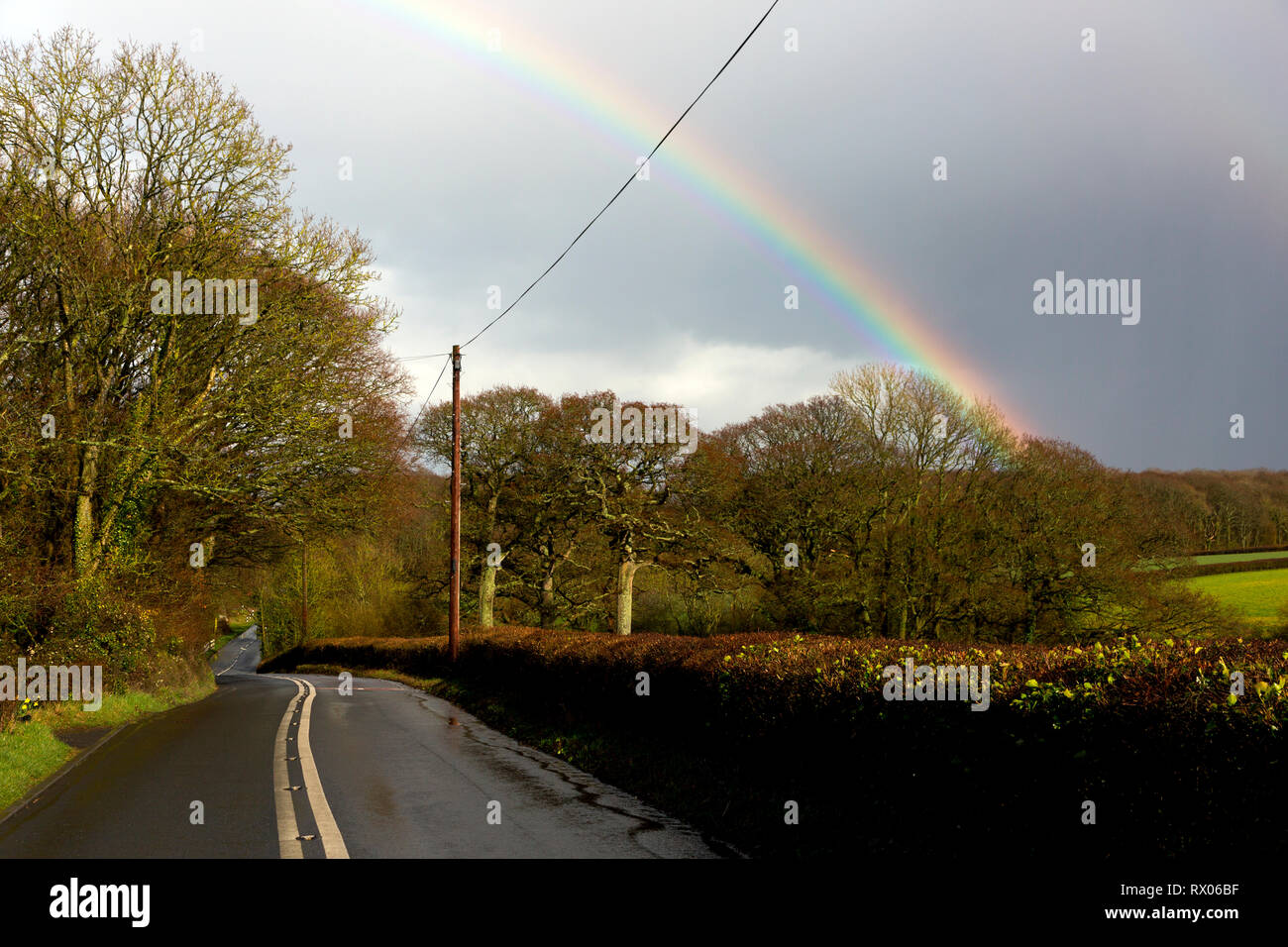 rainbow,rural,road,double,white,no,over,taking,lines,after,rain,storm,slippery,conditions,dangerous,country,village,speed,slippery,slide,crash,acciden Stock Photo