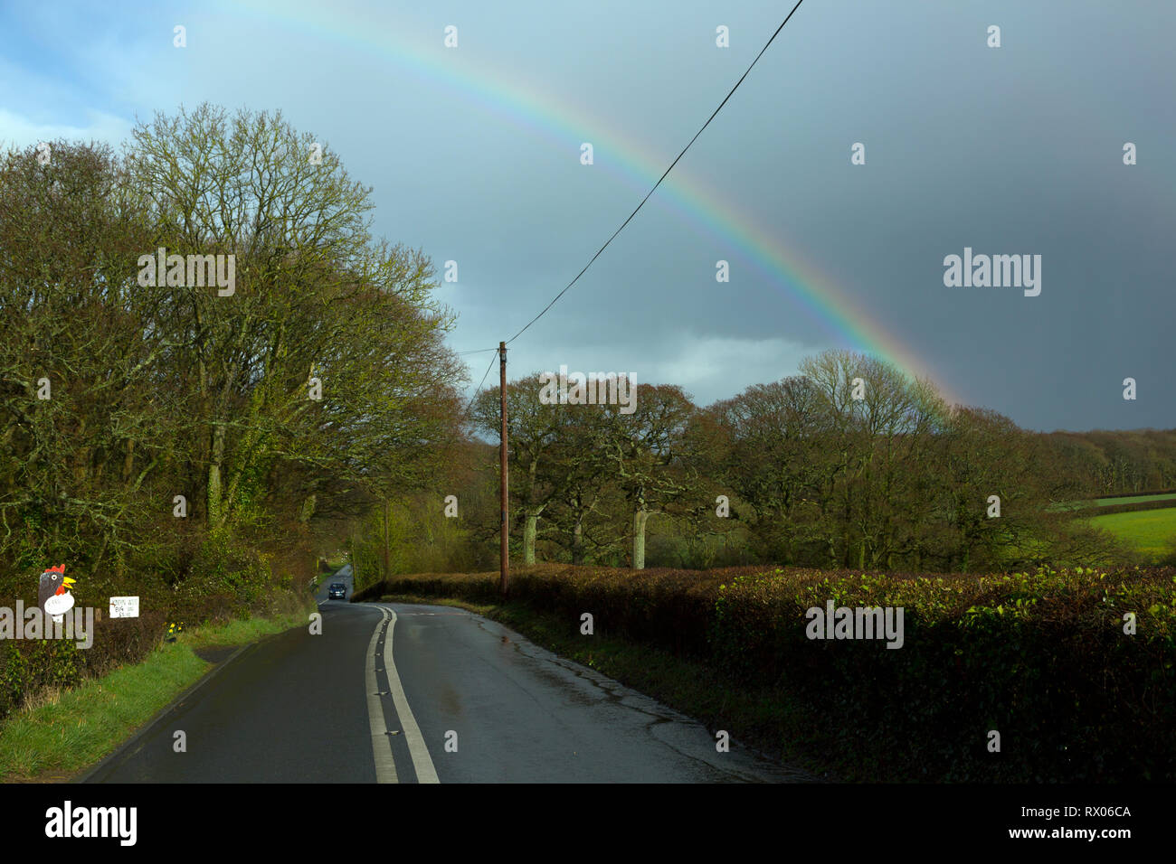 rainbow,rural,road,double,white,no,over,taking,lines,after,rain,storm,slippery,conditions,dangerous,country,village,speed,slippery,slide,crash,acciden - Stock Image