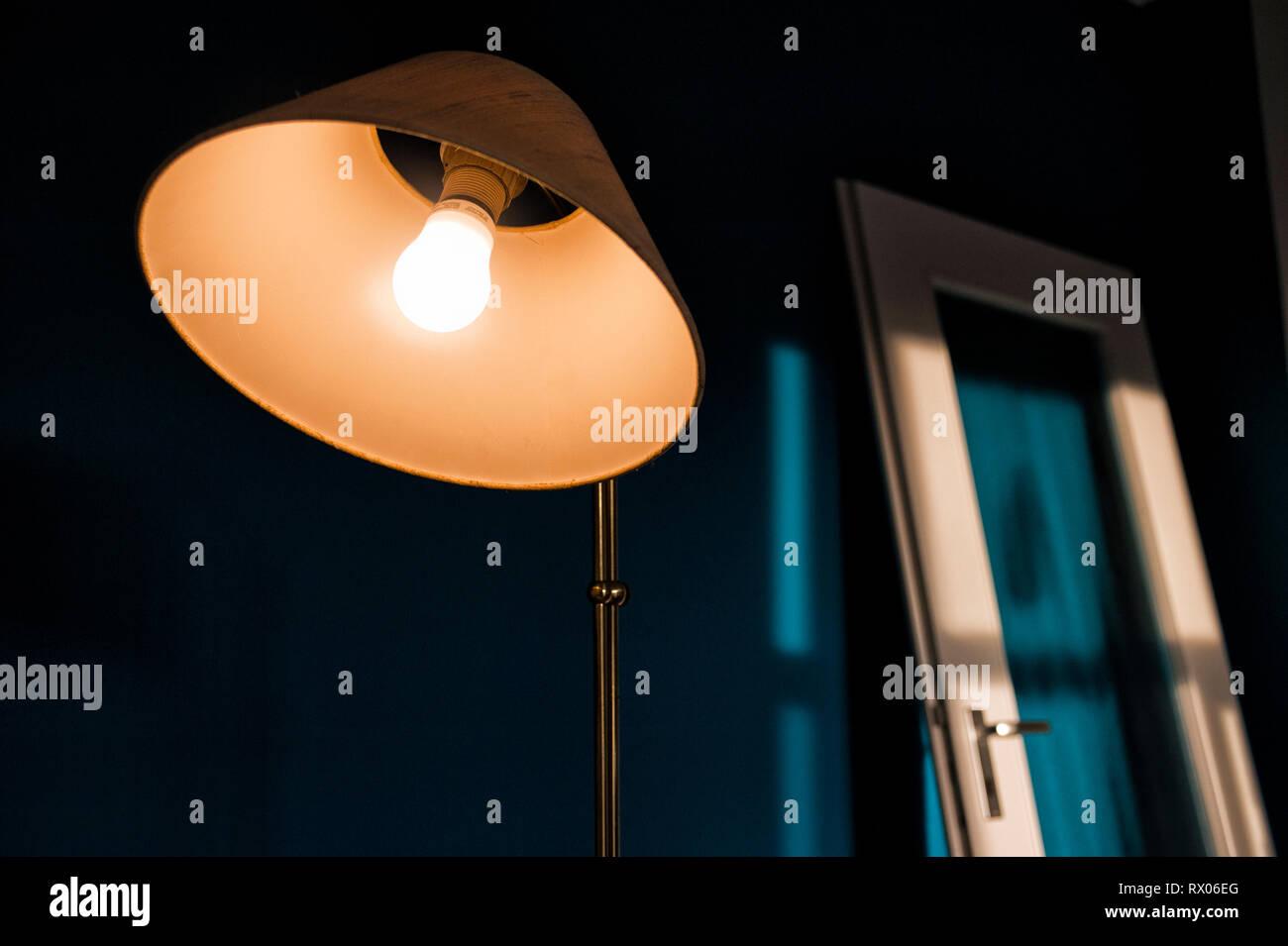 Im Vordergrund steht eine leuchtende 1960er Jahre Lampe. Im Hintergrund lehnt eine ausgehaengte Tuer an einer tuerkis gestrichenen Wand in der Sonne. - Stock Image