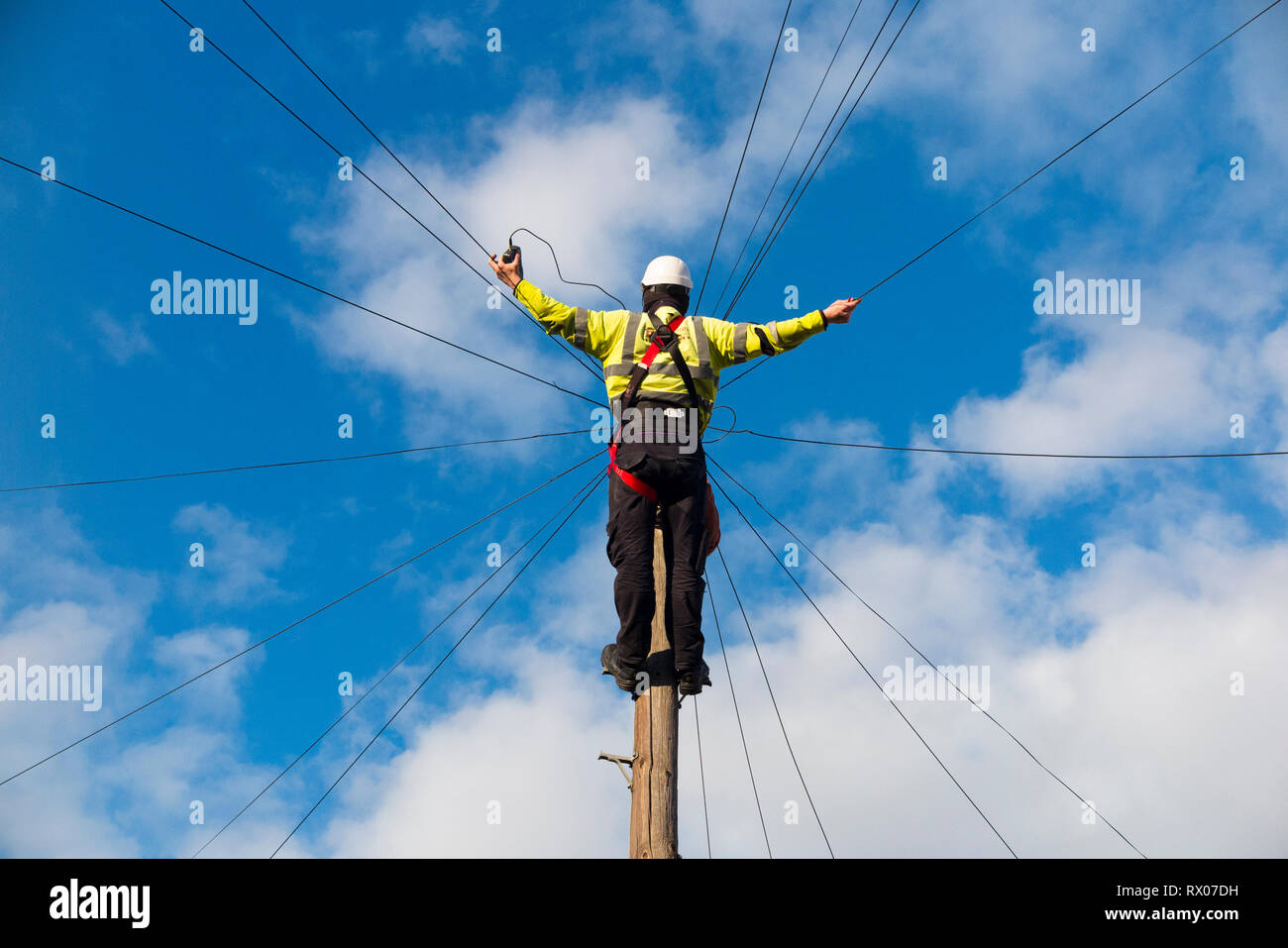 Telecom engineer working on domestic phone line / broadband internet copper wire up a telephone / telegraph pole in a London Street / Road, & blue sky - Stock Image