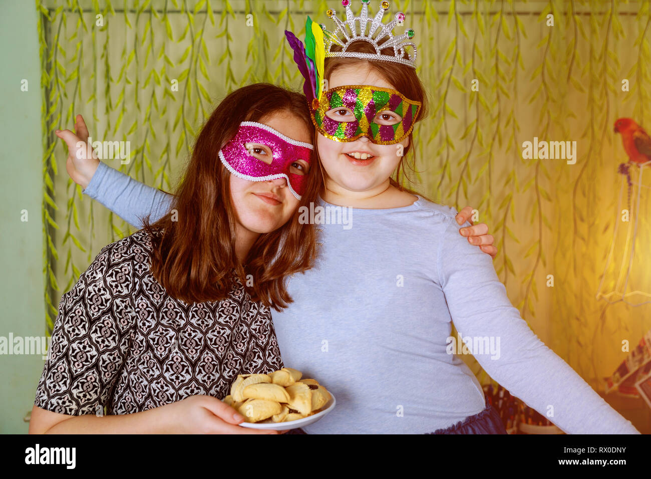 Jewish holiday Purim Happiness of fun and happy expressions In Festive Carnival Masks with hamantaschen cookies or hamans ears - Stock Image