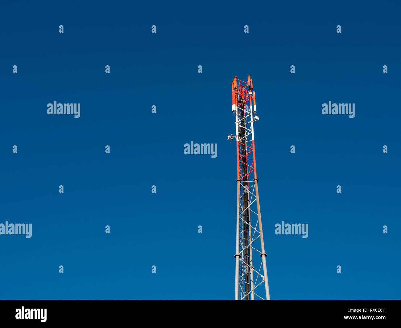 4G or GSM Antenna on a Red and White Mobile Telephone Mast against a Blue Sky - Stock Image