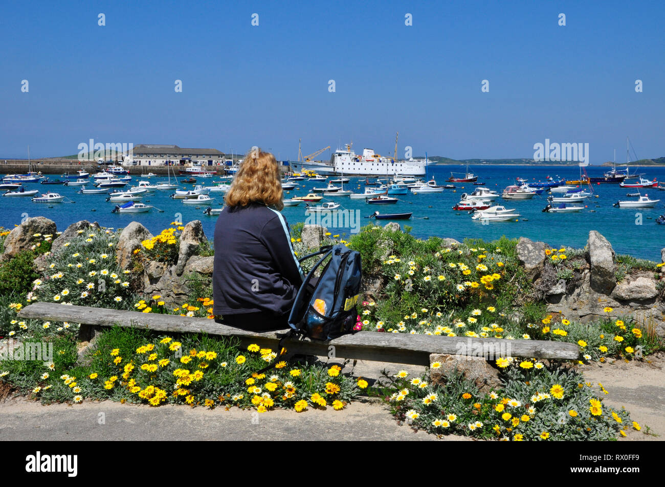 Holidaymaker enjoying the view across the crowded harbour at Hugh Town, St Mary's, Isles of Scilly. While Scillonian 3 is being unloaded after it jour - Stock Image