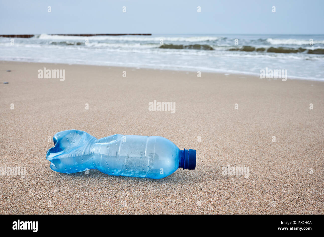Plastic bottle left on a beach, selective focus, color toning applied. - Stock Image