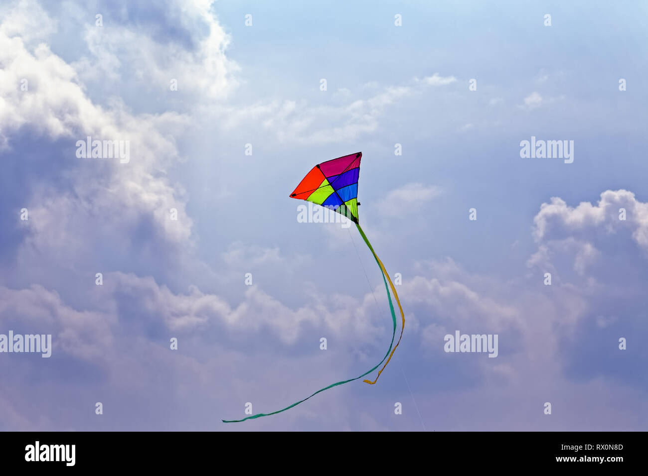 42,518.02980 kite with long curved tail, multi-color multi colored red yellow green blue purple triangular kite flying in sunny cloudy blue sky clouds - Stock Image