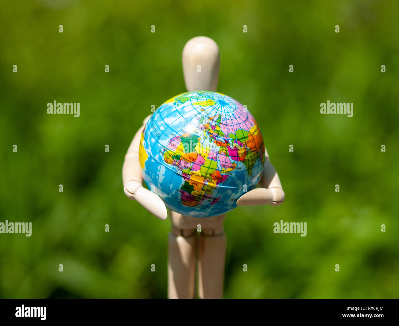 A wooden mannequin with a world ball in his arms. Ecology concept, globalization - Stock Image