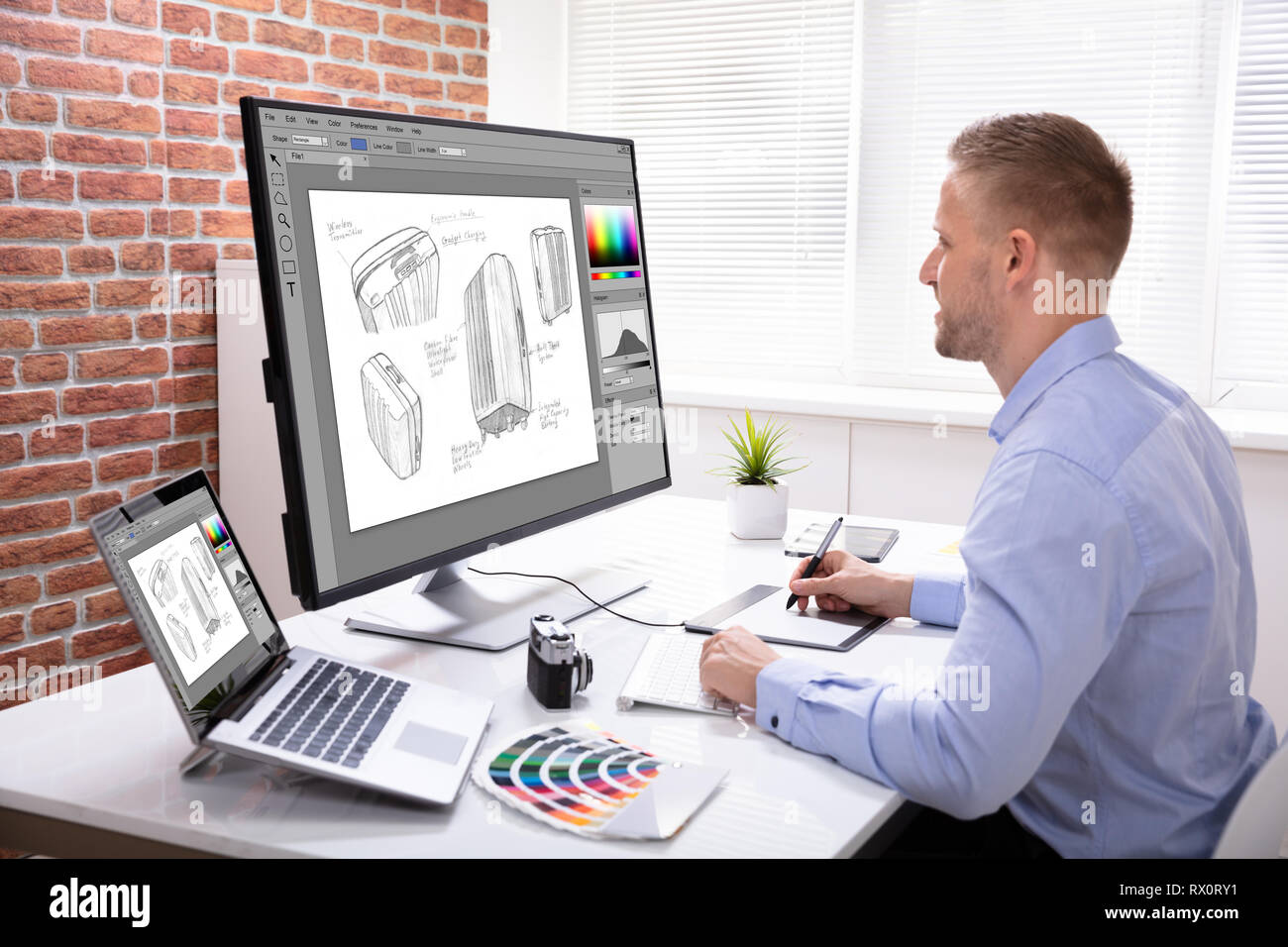 Side View Of Designer Drawing Suitcase On Computer Using Graphic Tablet In Office Stock Photo