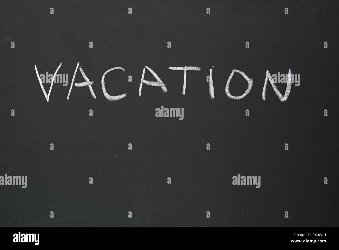 vacation hand written in chalk on a blackboard - Stock Image