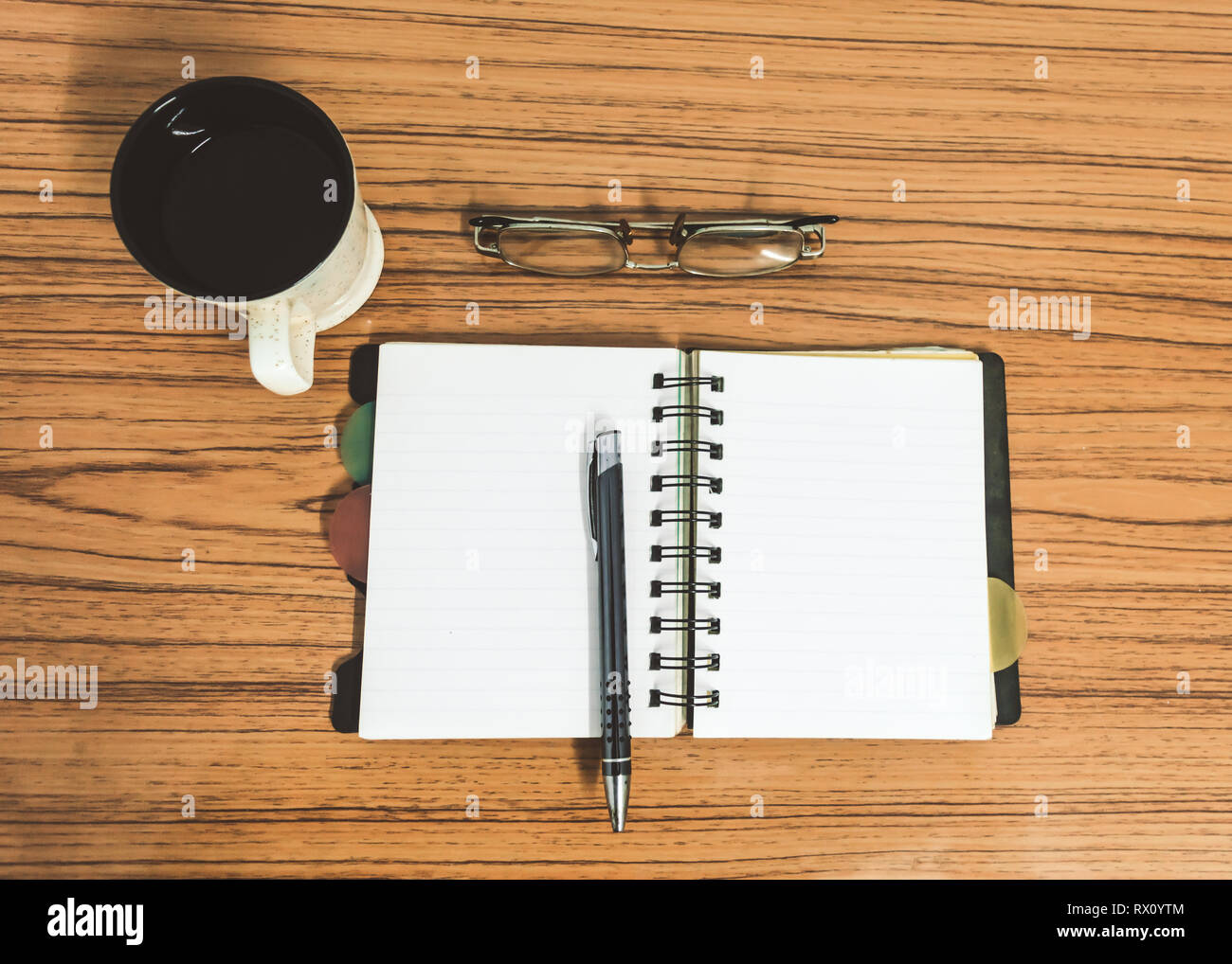Desk with open notebook with blank pages, eye glasses, pen and a cup of coffee. Top view with copy space. Business still life concept with office stuf - Stock Image