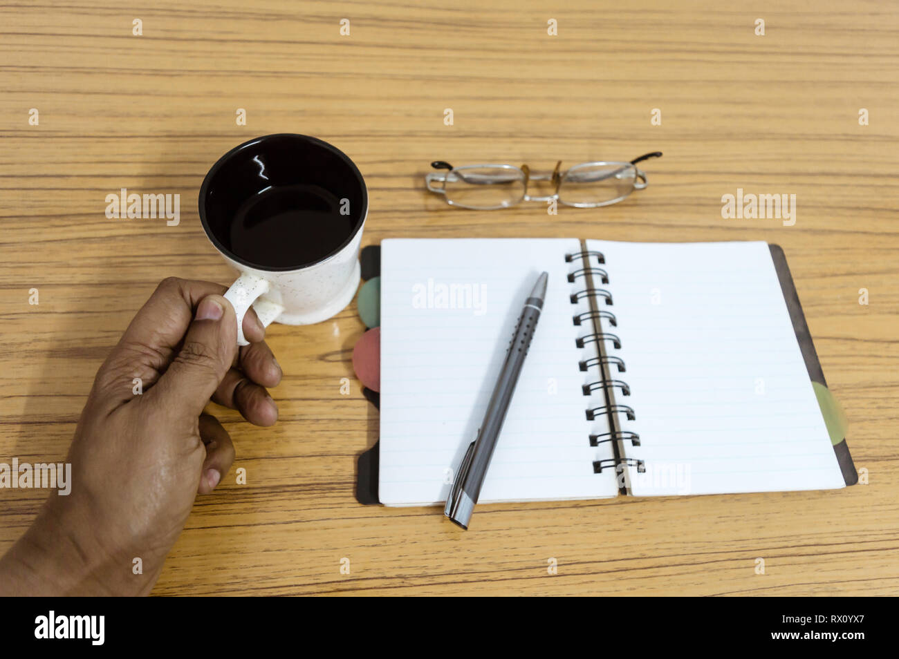 Businessman holding a cup of coffee. Business pocket planner with a eyeglass and a pen ready to note an appointment. Business still life concept with  - Stock Image