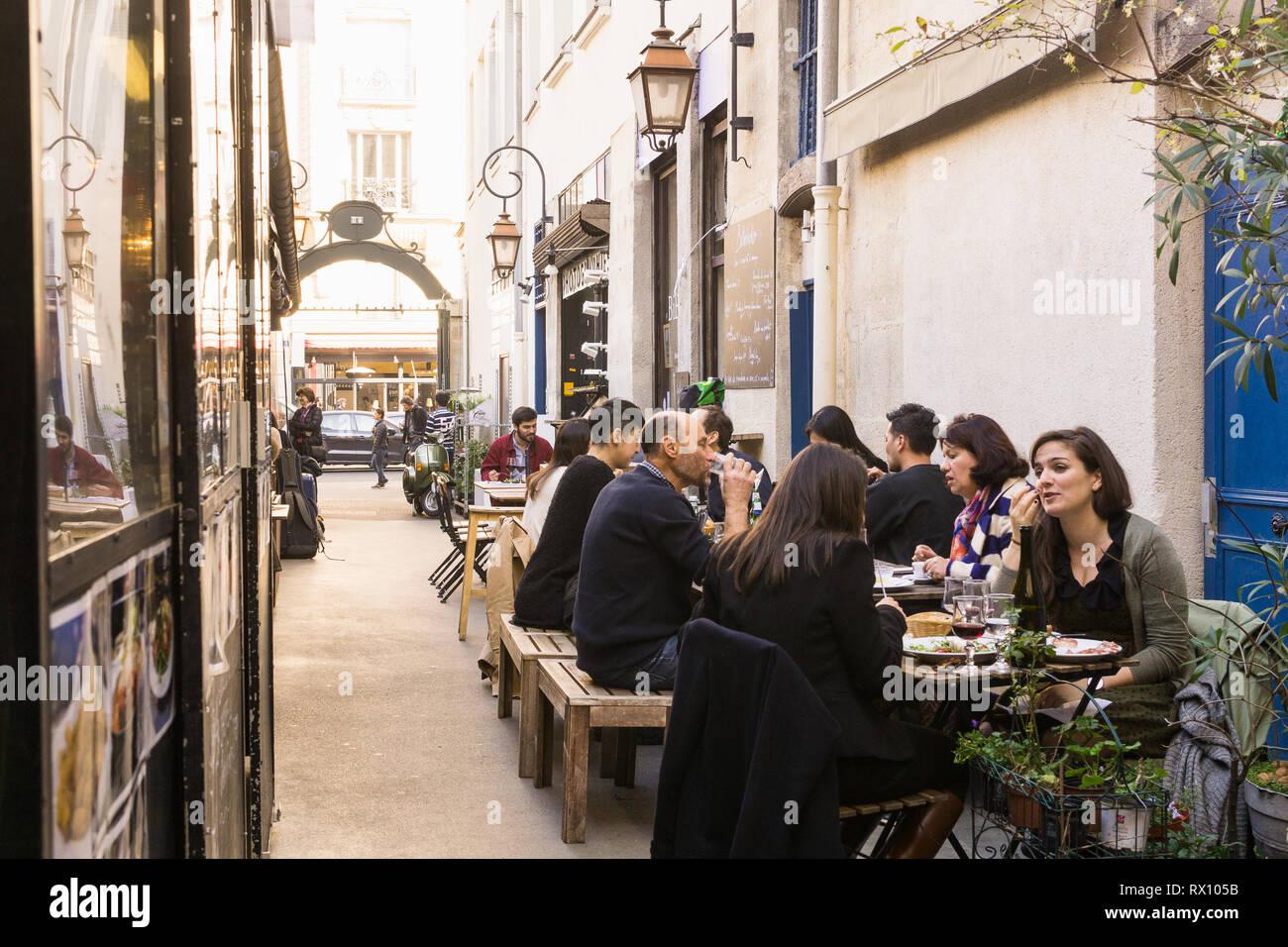 Paris food market - People having lunch break in eateries at the Marche des Enfants Rouges in the Marais district of Paris, France. Stock Photo