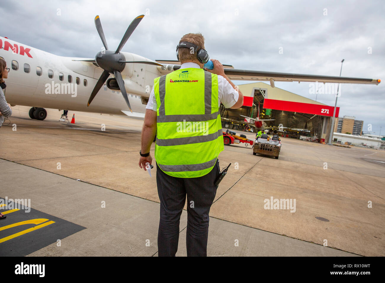 Qantas Link employee in high viz vest  airside at Sydney airport awaits luggage to be unloaded from an inbound Qantas flight plane,Sydney,Australia - Stock Image