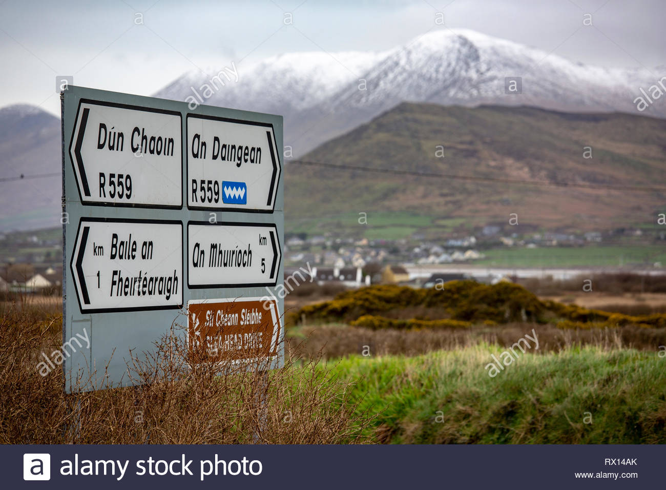 Snow on the mountains in the Irish-speaking area of West Kerry as a sign shows the way to the villages in the area. - Stock Image