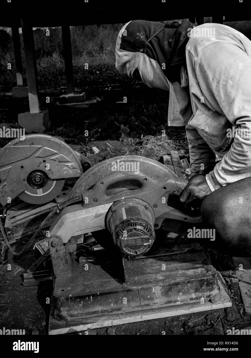 Male worker cutting steel with a cutting machine - Stock Image