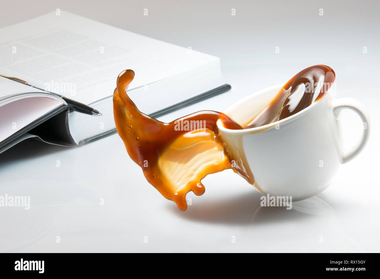 Falling and spilling of a cup of coffee on top of a desk with an open book - Stock Image