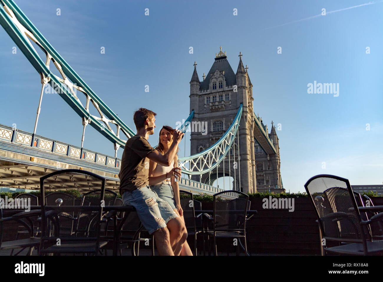 Couple enjoy sunset with beer and water sittin on a table. Tower bridge on the back - Stock Image