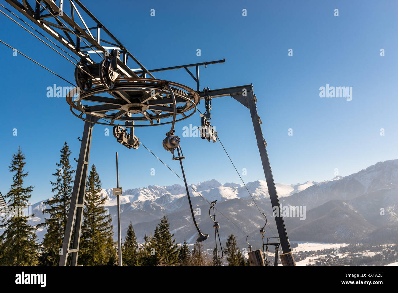 The mechanism of the ski lift, visible large, driving wheel pulling the rope and suspended chairs in the background Tatra Mountains and trees. - Stock Image