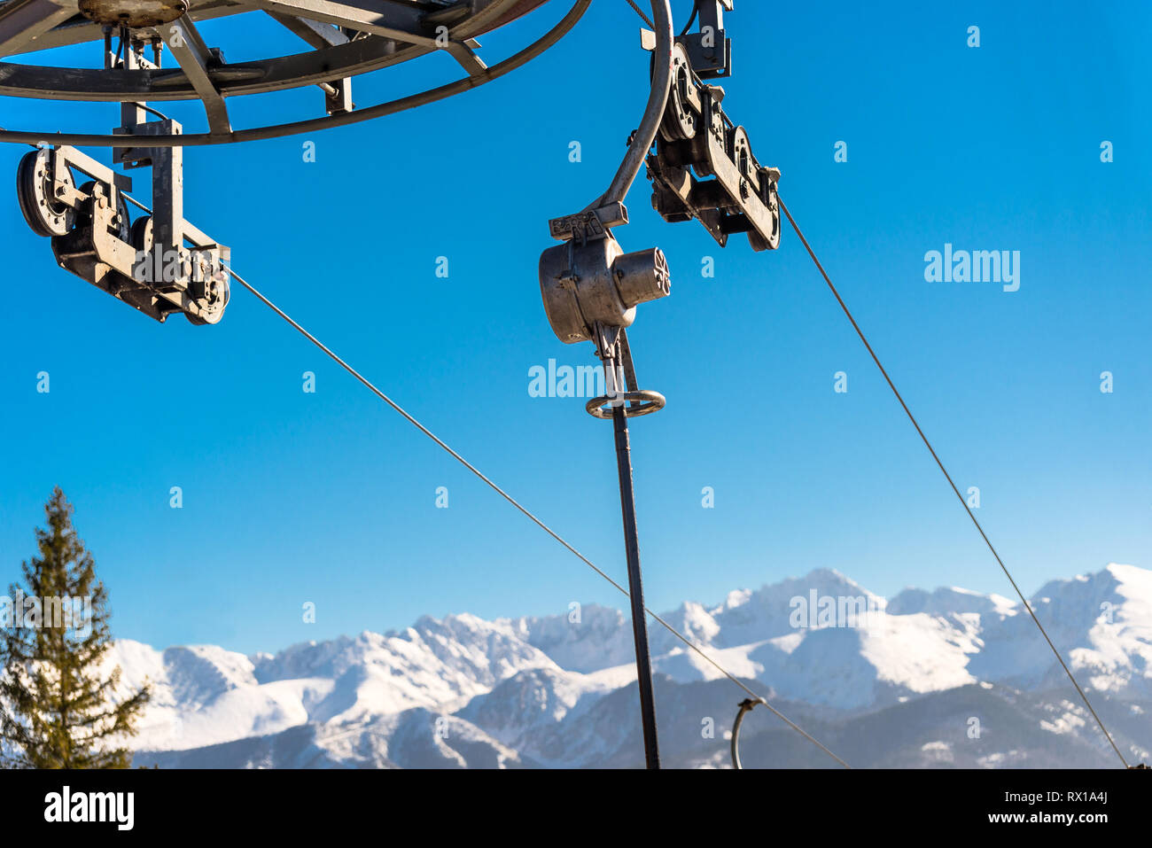 The mechanism of the ski lift, visible metal parts and ropes on which hang chairs in the background Tatry mountains. - Stock Image
