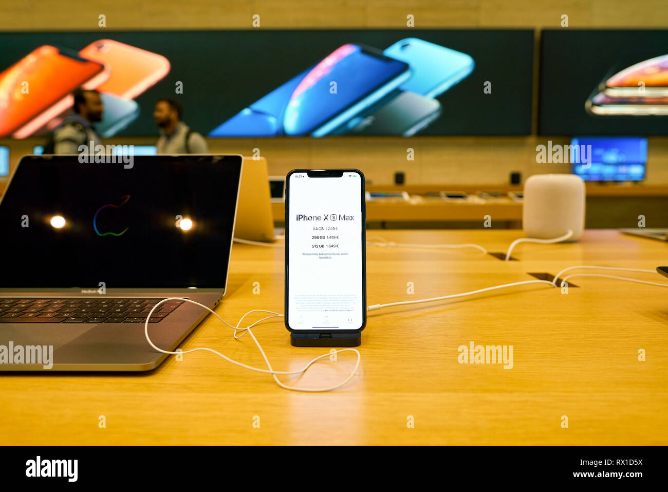 DUSSELDORF, GERMANY - CIRCA SEPTEMBER, 2018: MacBook Pro and iPhone XS Max on display at Apple store in Dusseldorf. - Stock Image