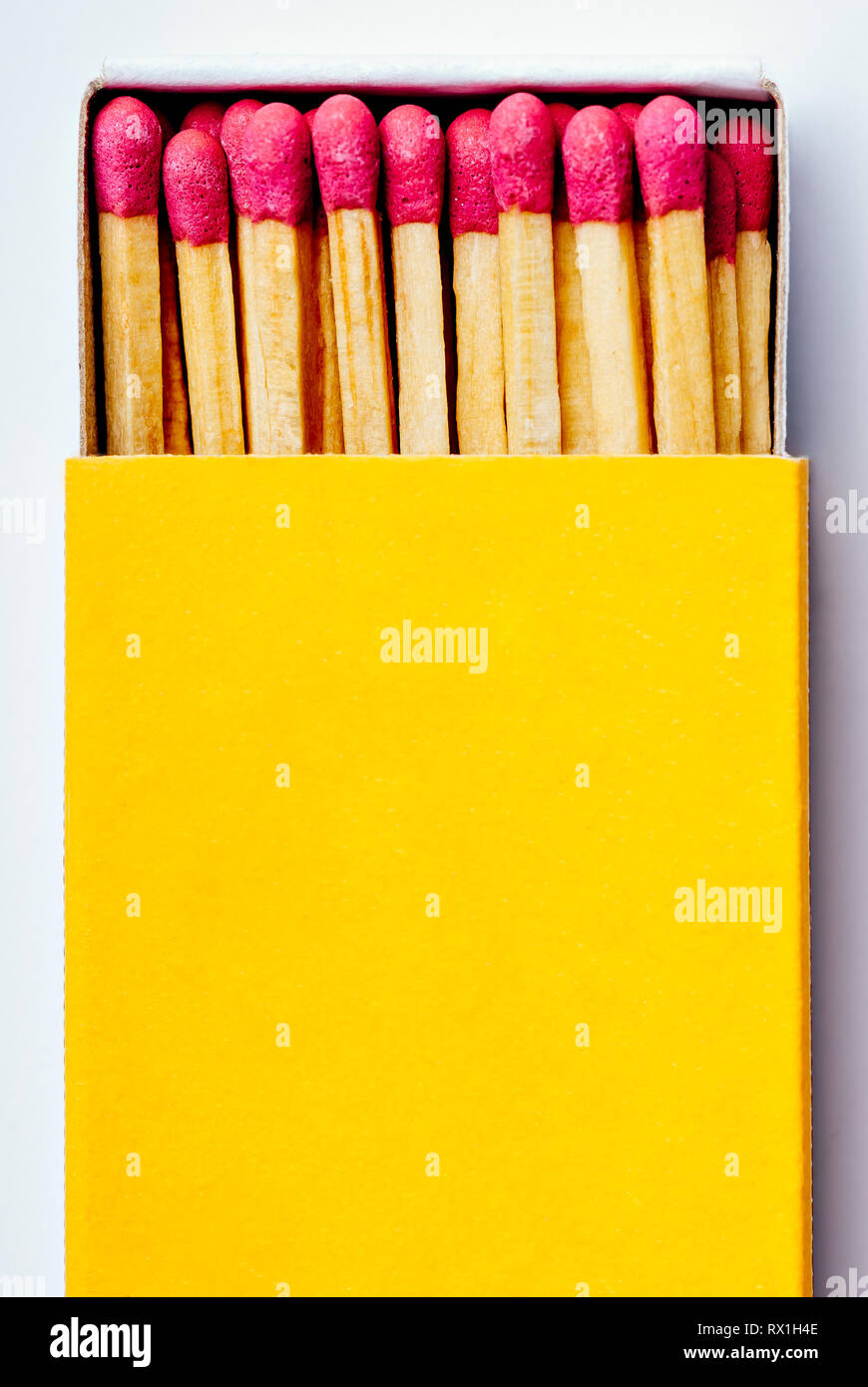 Brand new open yellow matchbox with many pink match sticks in it - Stock Image