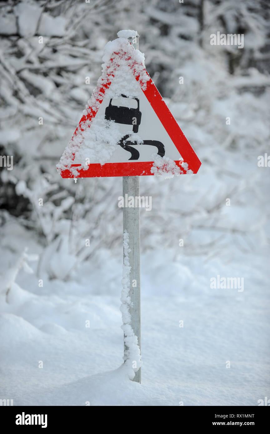 UK road traffic sign warning of slippery roads. Stock Photo