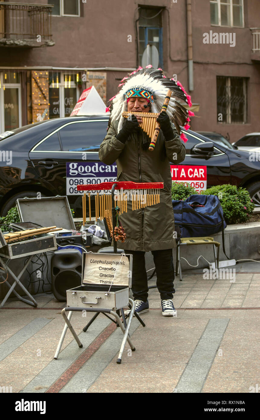 Yerevan,Armenia,December 03,2018:On the street of Yerevan musician in a headdress of feathers, playing a melody on the pan flute with Peruvian ethnic  - Stock Image
