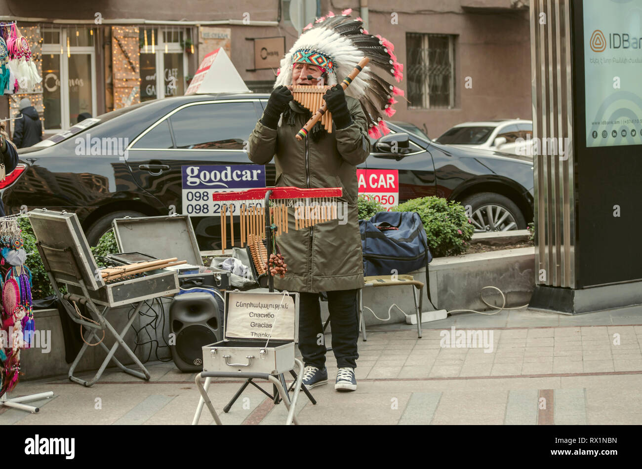 Yerevan,Armenia,December 03,2018:Peruvian musician in a feather headdress, playing a pan-flute melody with ethnic motifs on the streets of Yerevan - Stock Image