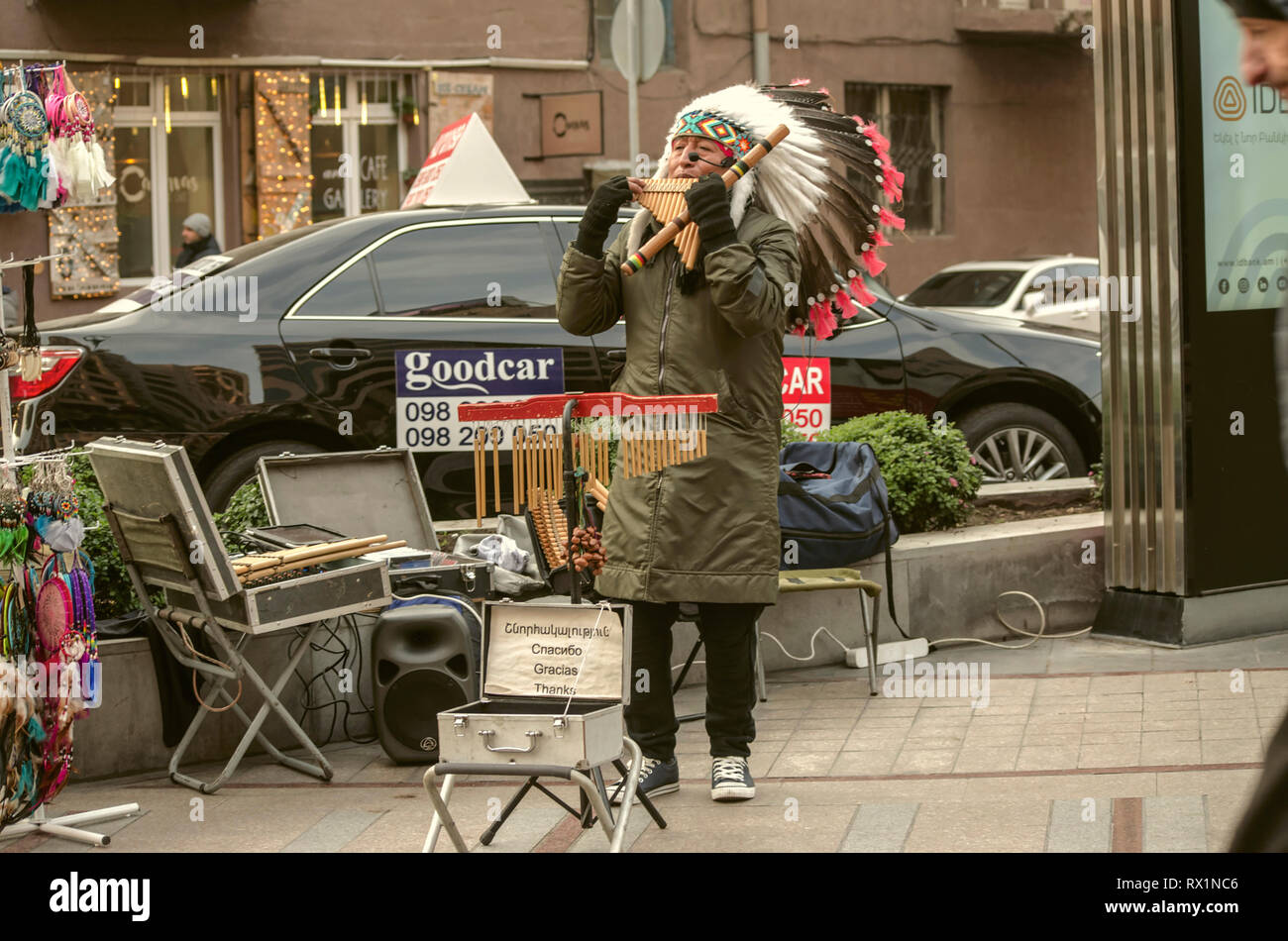 Yerevan,Armenia,December 03,2018:On Yerevan street, a middle-aged man in a feather headdress plays a pan flute melody with ethnic Peruvian motifs - Stock Image