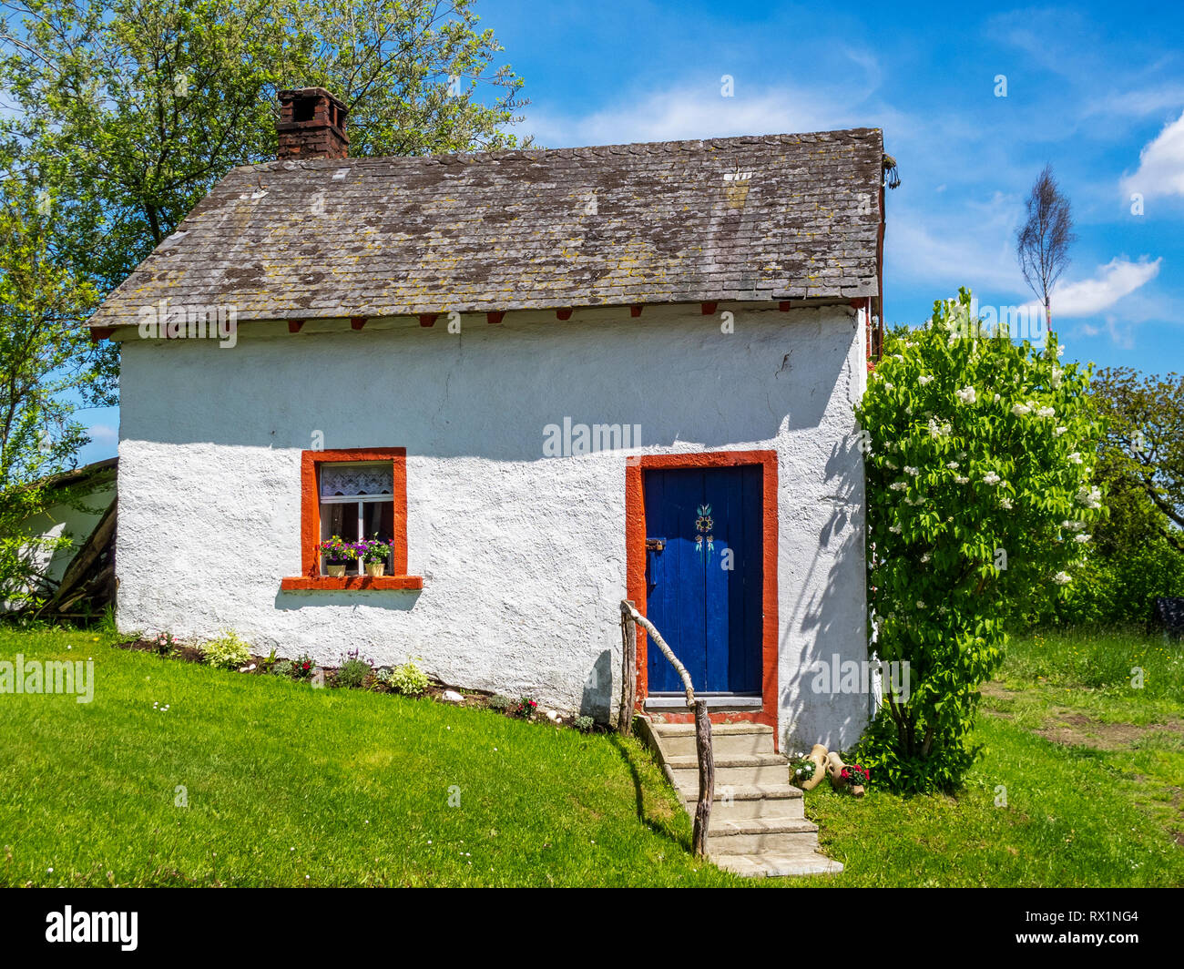 Beautiful cottage in Herresbach, Germany on a sunny summer day, a maypole or Maibaum in the distance - Stock Image