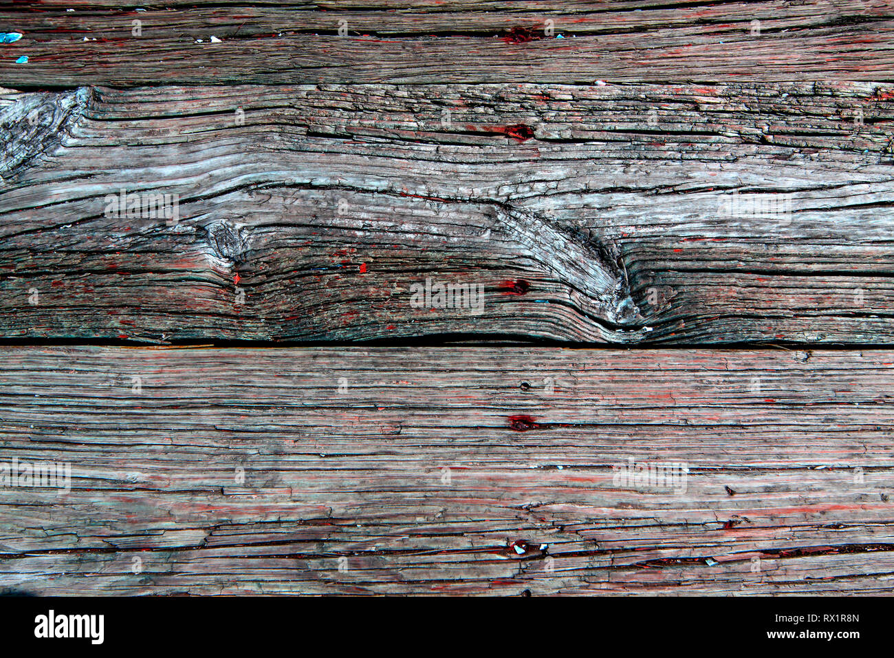 Weathered decking close up with worn red paint and nail heads - Stock Image
