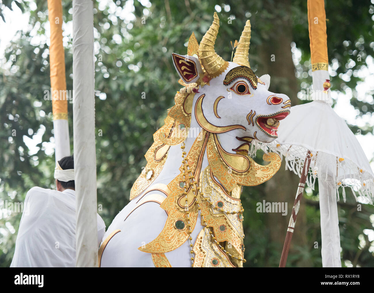 Rear view of man sitting by bull sculpture against trees during cremation ceremony - Stock Image