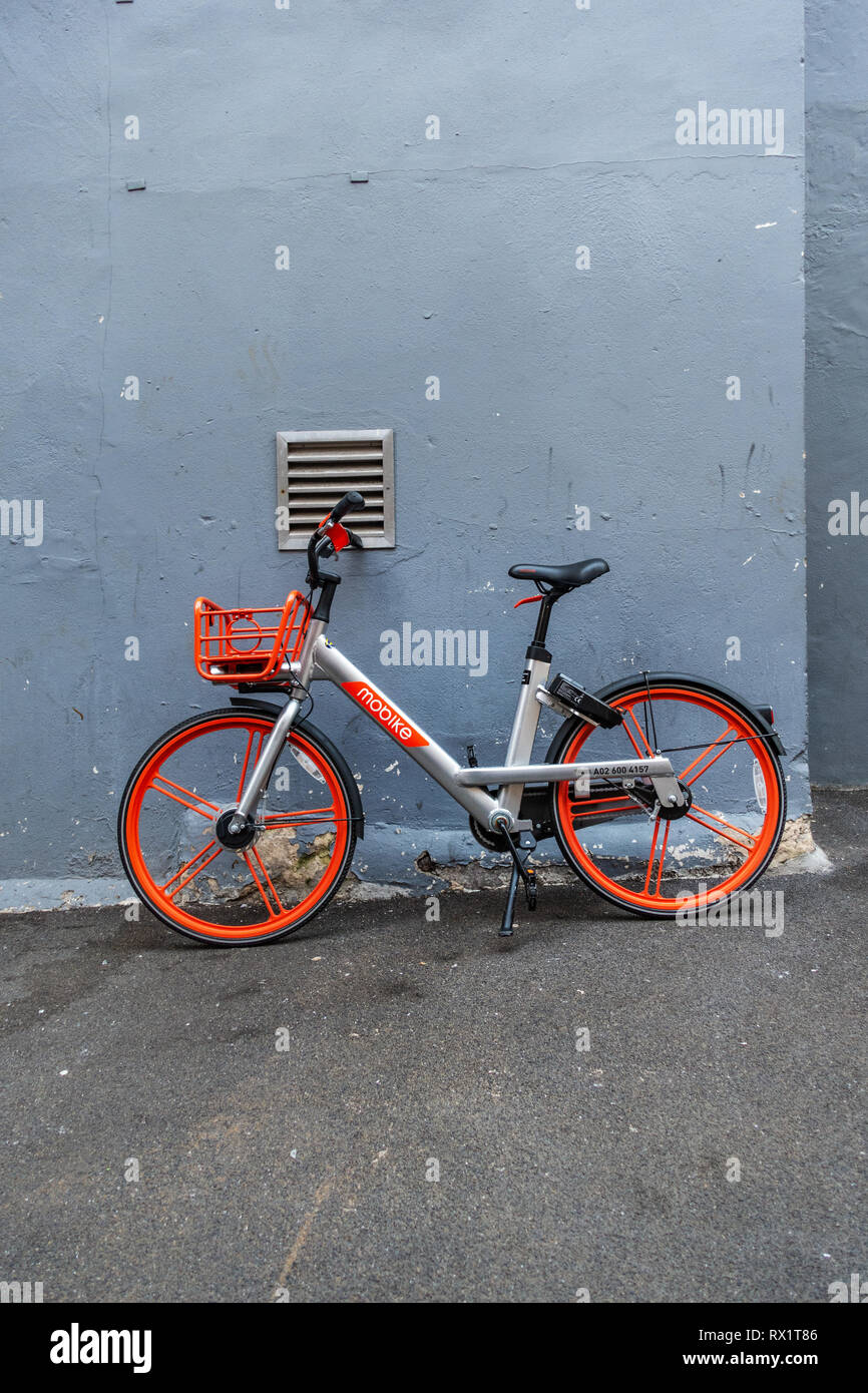 Bike sharing with shared transportation for convenient short urban trips on this Mobike hire pushbike leaning against a wall in Soho, London - Stock Image
