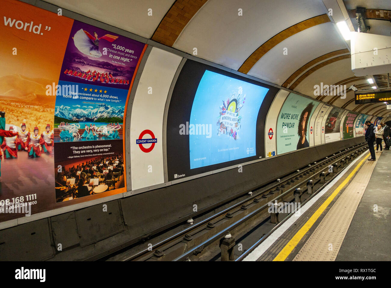 Tube train Underground Track with ad poster Billboard Advertising posters on the Underground Tube at Covent Garden, London - Stock Image
