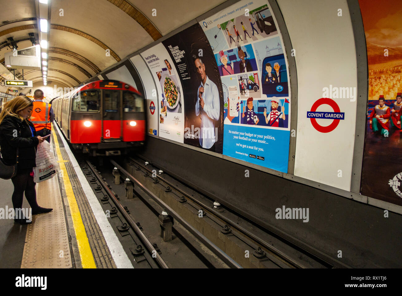 Female Commuter waits for the approaching tube train on london underground track with ad poster - Stock Image