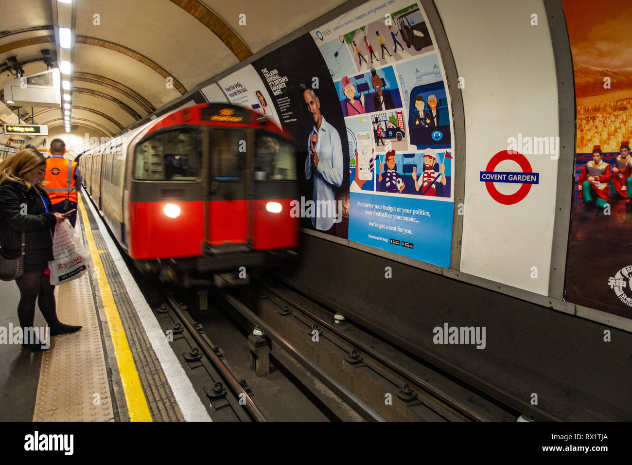 Female Commuter waits for the approaching tube train on a london underground station with ad poster on wall - Stock Image