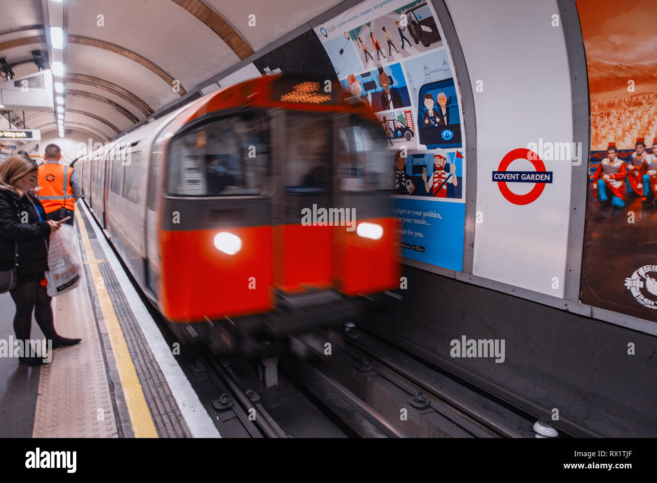 Female Commuter waits for the approaching tube train on london underground track passing ad poster - Stock Image