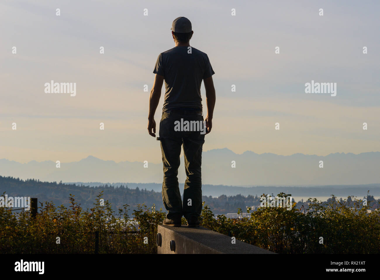 Rear view of man looking at view while standing on retaining wall against cloudy sky during sunset Stock Photo