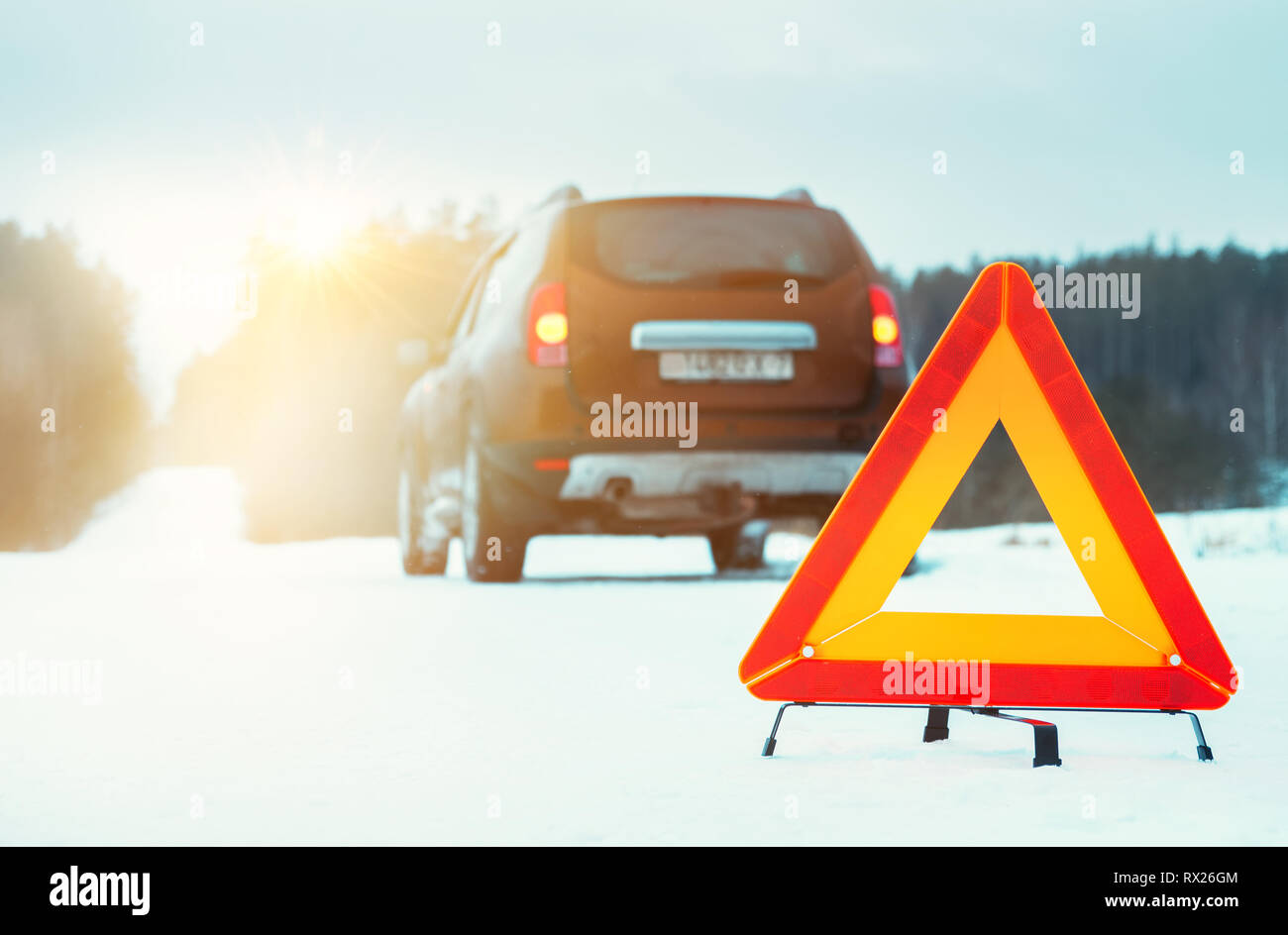 Emergency stop sign and car on winter road at sunset. - Stock Image