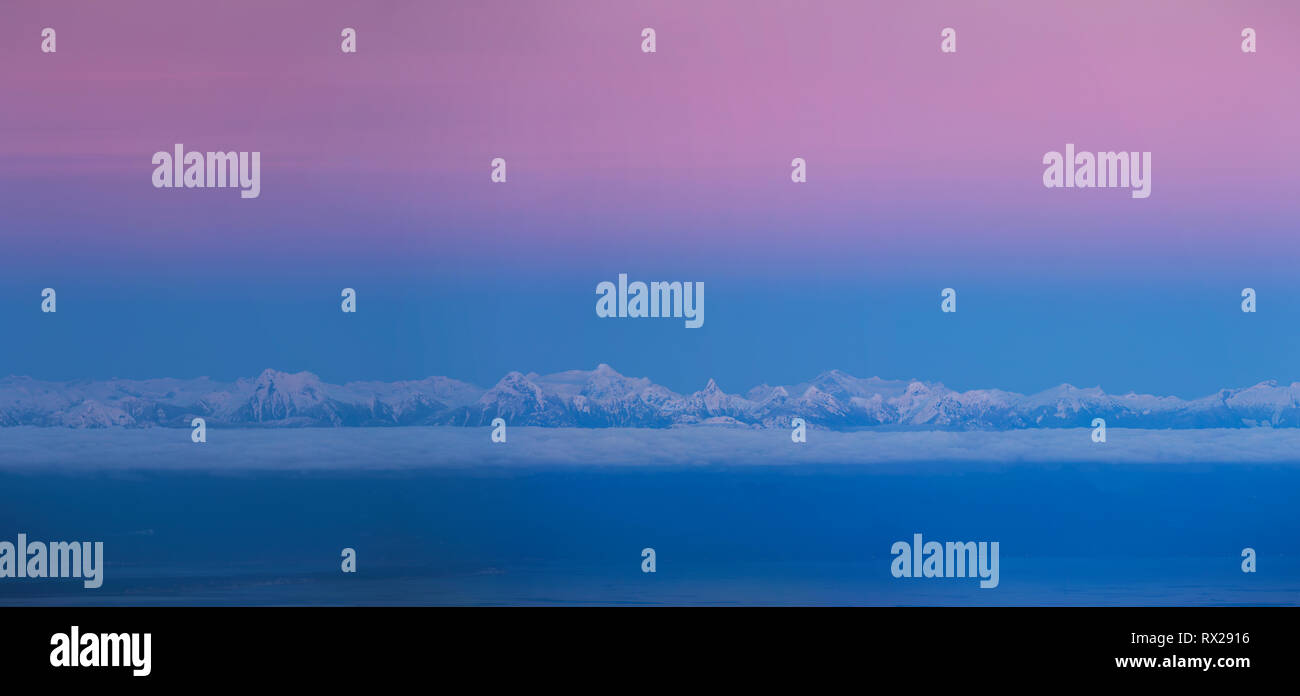 Cold color hues settle over the British Columbia Coast Range after sunset.  Coast Mountains, British Columbia, Canada - Stock Image