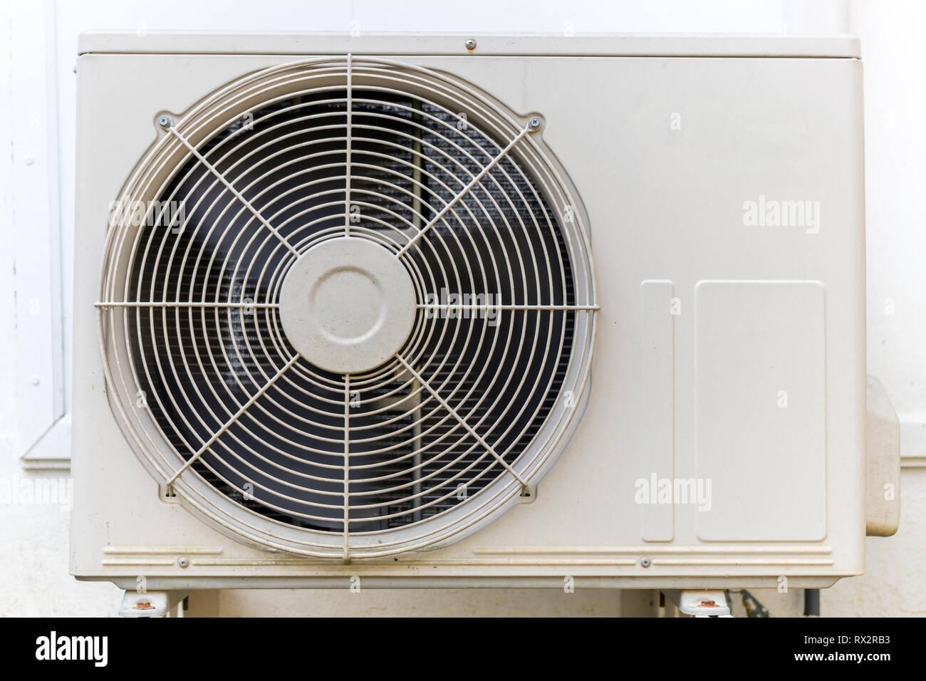 Condenser air conditioner compressor unit on concrete wall. Stock Photo