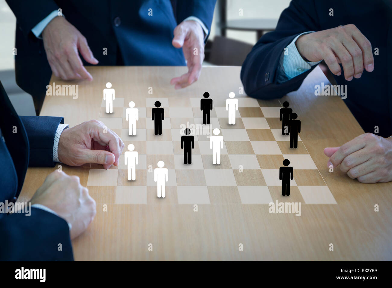 Three business administrators playing checkers or draughts on a wooden checkerboard or draughtboard in concept of manpower or human resource. Stock Photo