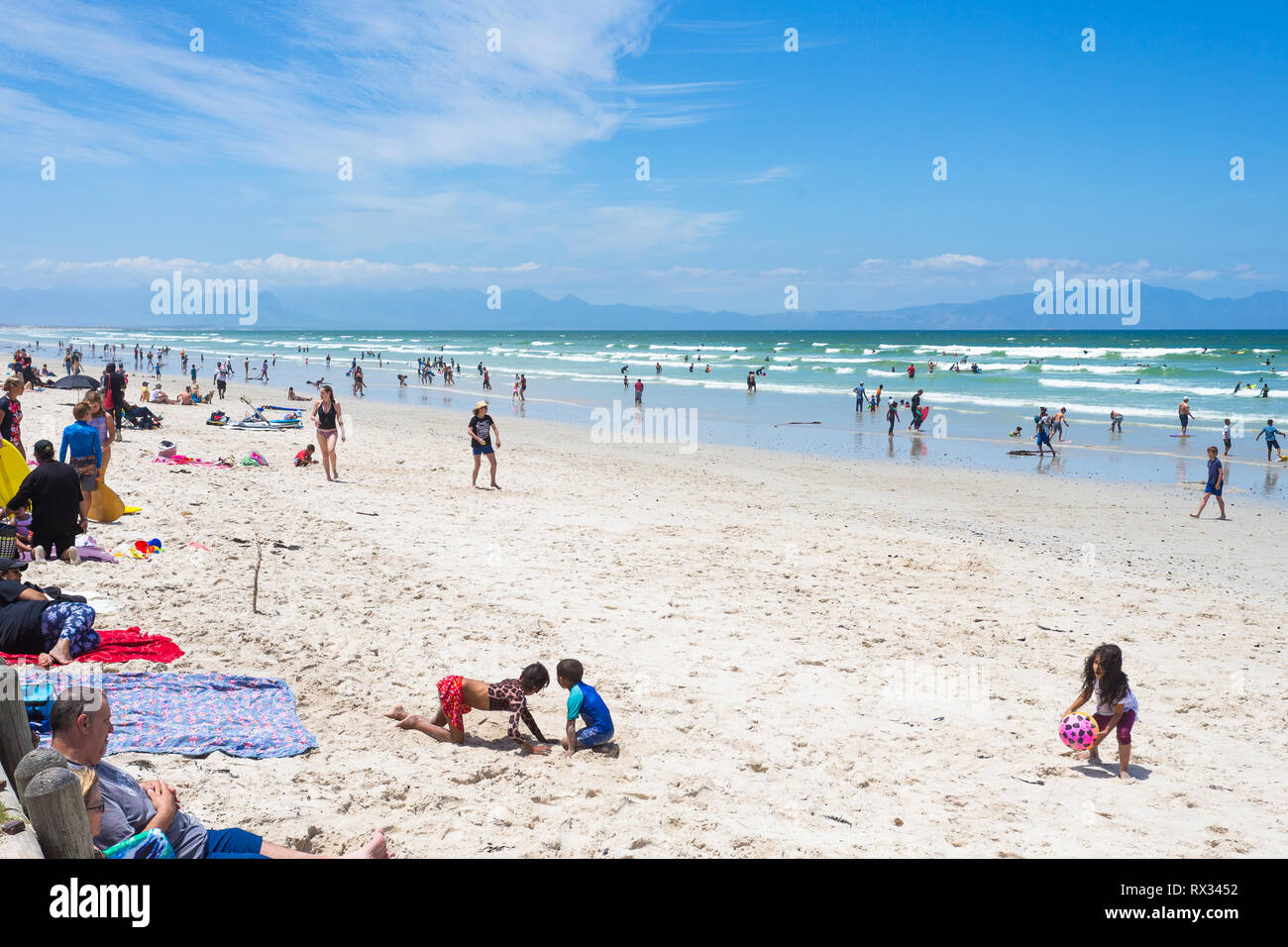 a busy beach day with crowds of beachgoers enjoying themselves on a hot Summer day at Muizenberg, False bay, Cape Peninsula, Cape Town, South Africa - Stock Image