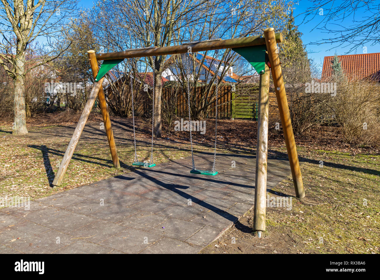Swing on a deserted playground in late autumn - Stock Image