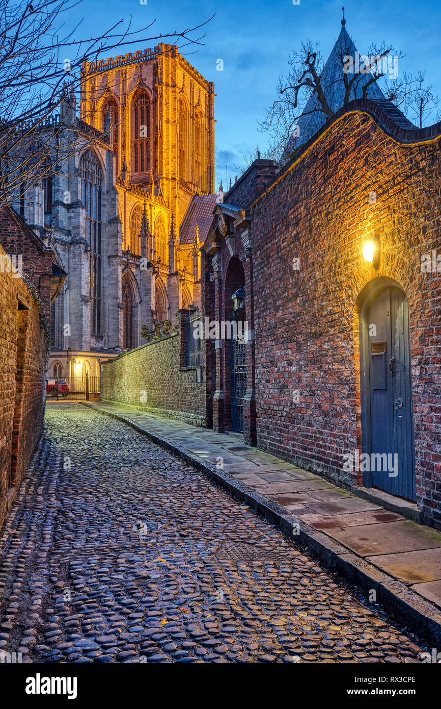 Small cobbled street in York at night with the famous Minster in the back Stock Photo