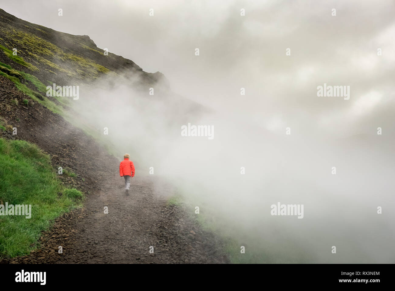 Boy bravely journeys alone on Iceland adventure in steamy valley - Stock Image
