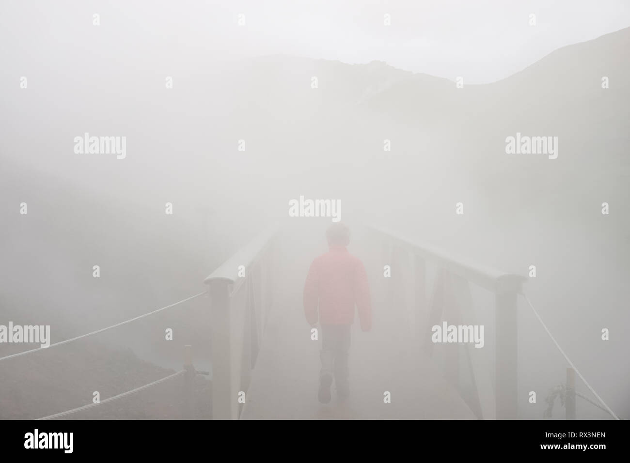 Boy alone walking into the unknown on Iceland adventure in steamy valley - Stock Image