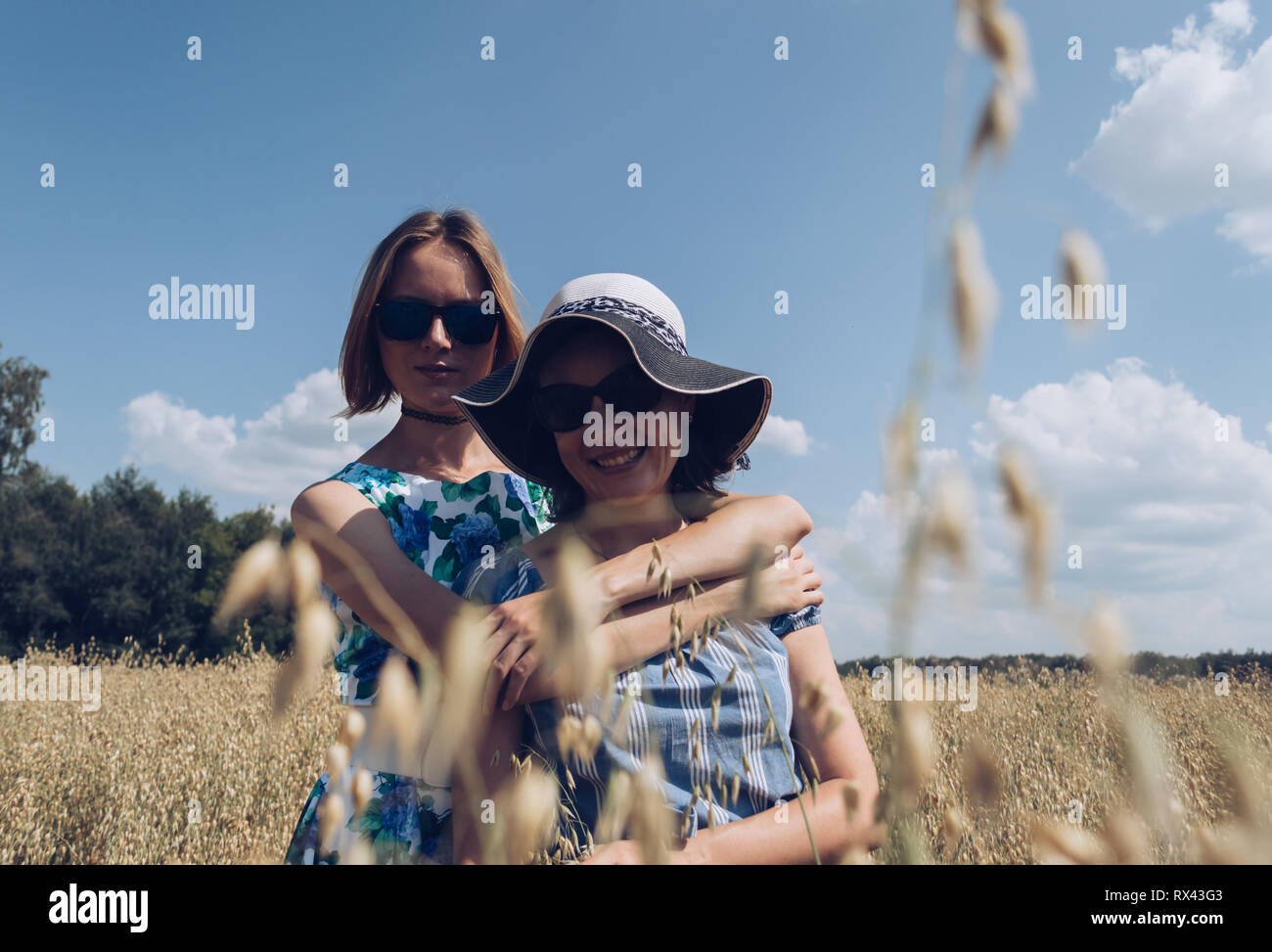 retro styled photo of hugging female friends standing in oat field on hot summer day - Stock Image