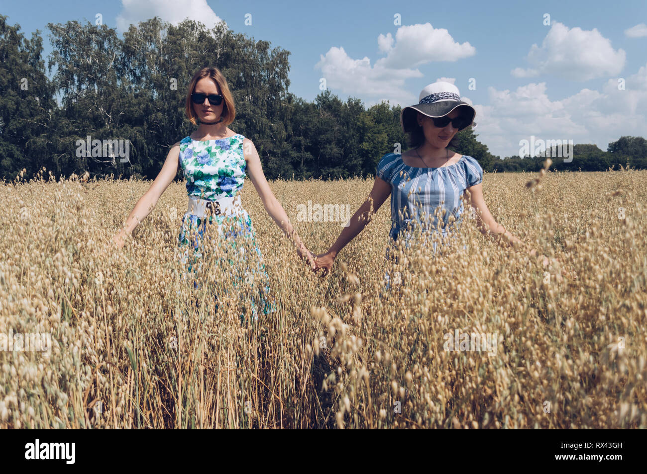 walking through oat field female friends on hot summer day - Stock Image
