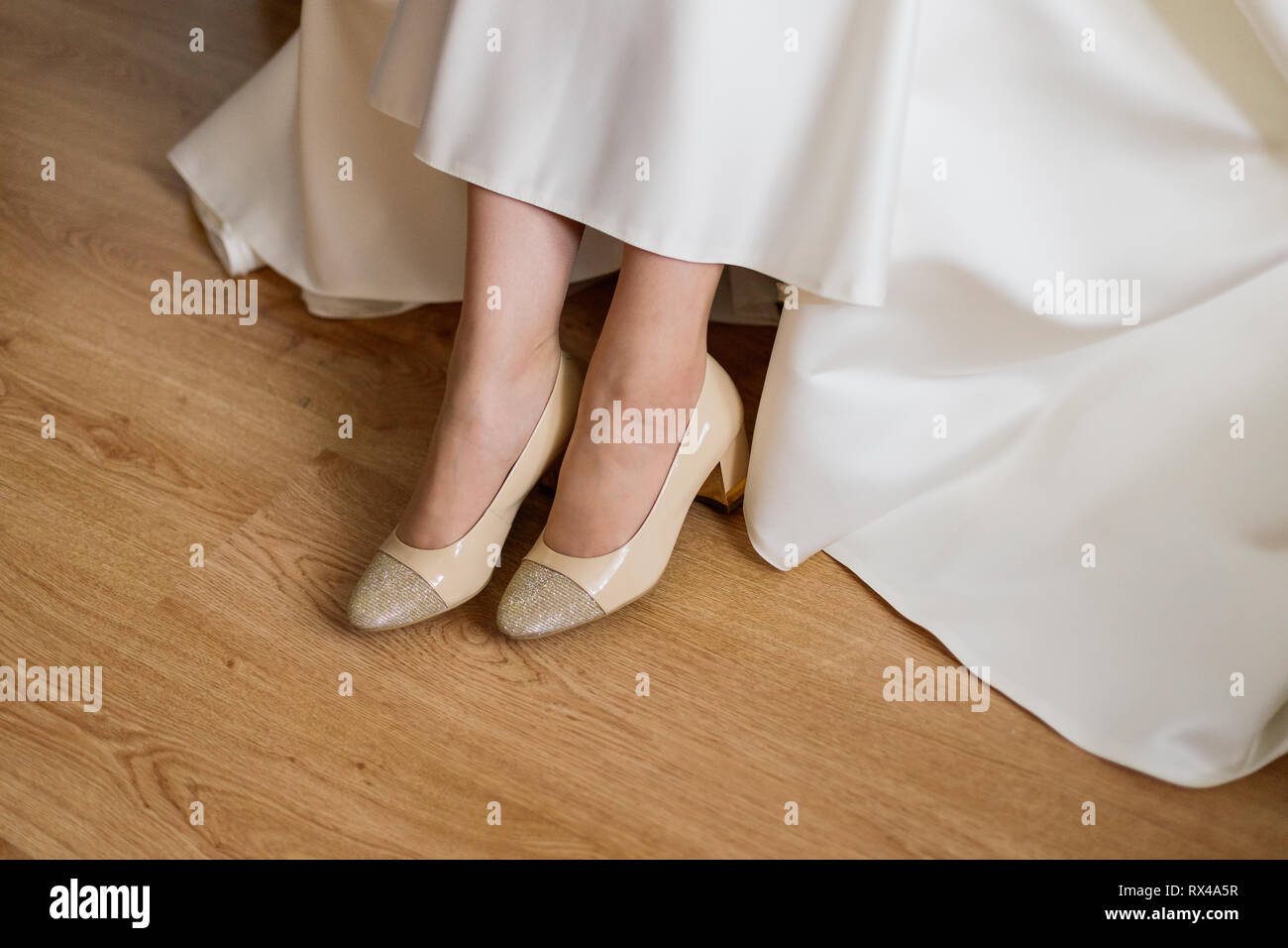 Closeup of bare feet of a bride on a wooden surface. Wedding background with free place for text - Stock Image