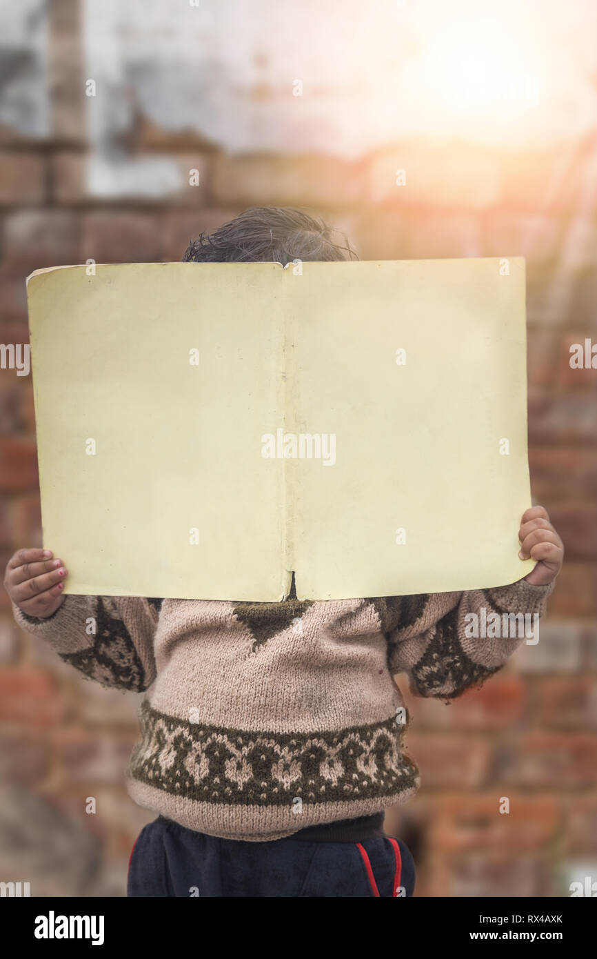 Portrait of Cute 2 year little Indian Asian baby girl holding and looking at picture book - Stock Image